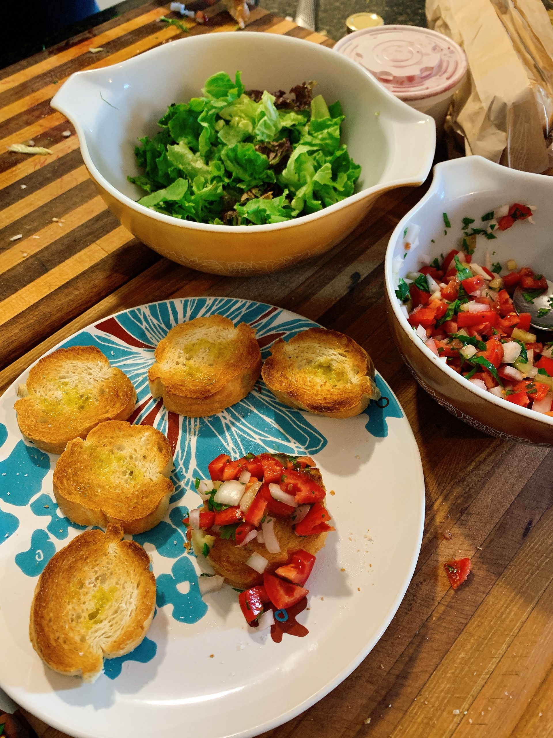 Sliced baguette, homemade salsa, and a bowl of greens.