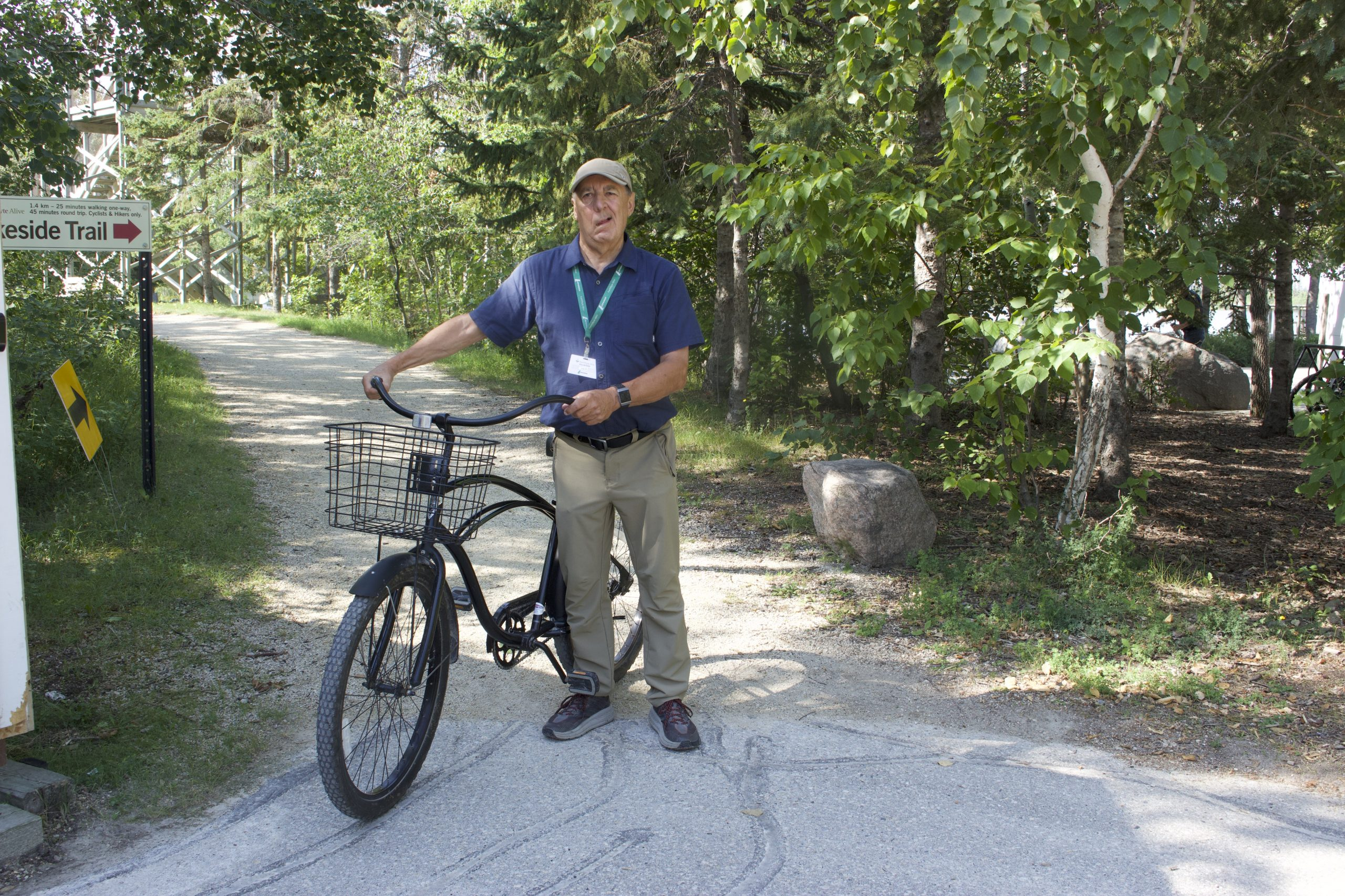 Lou stands beside a bike on a trail surrounded by green trees.