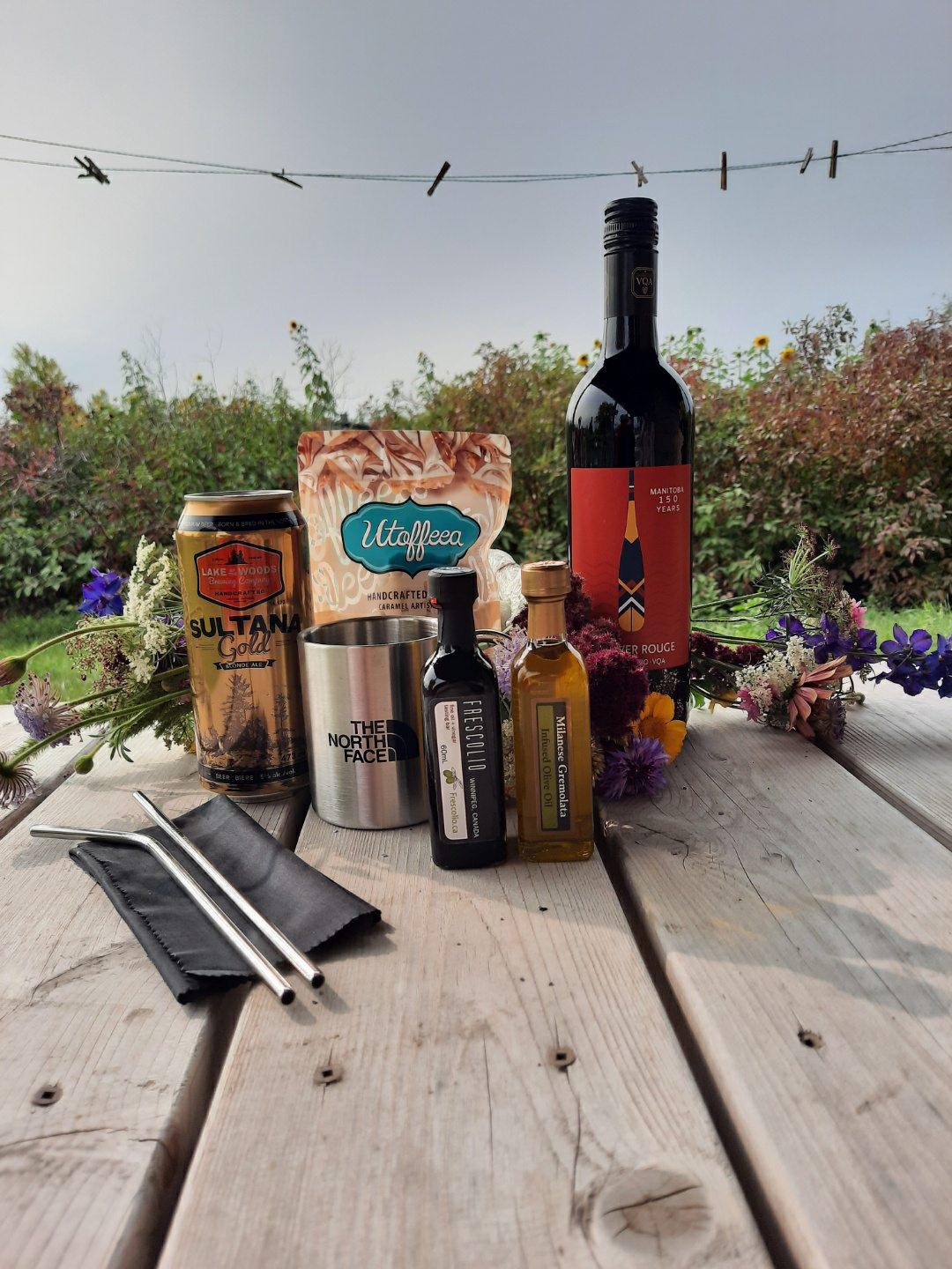 Wine, desserts, reusable cutlery, a mug, and more are clustered together on a picnic table.