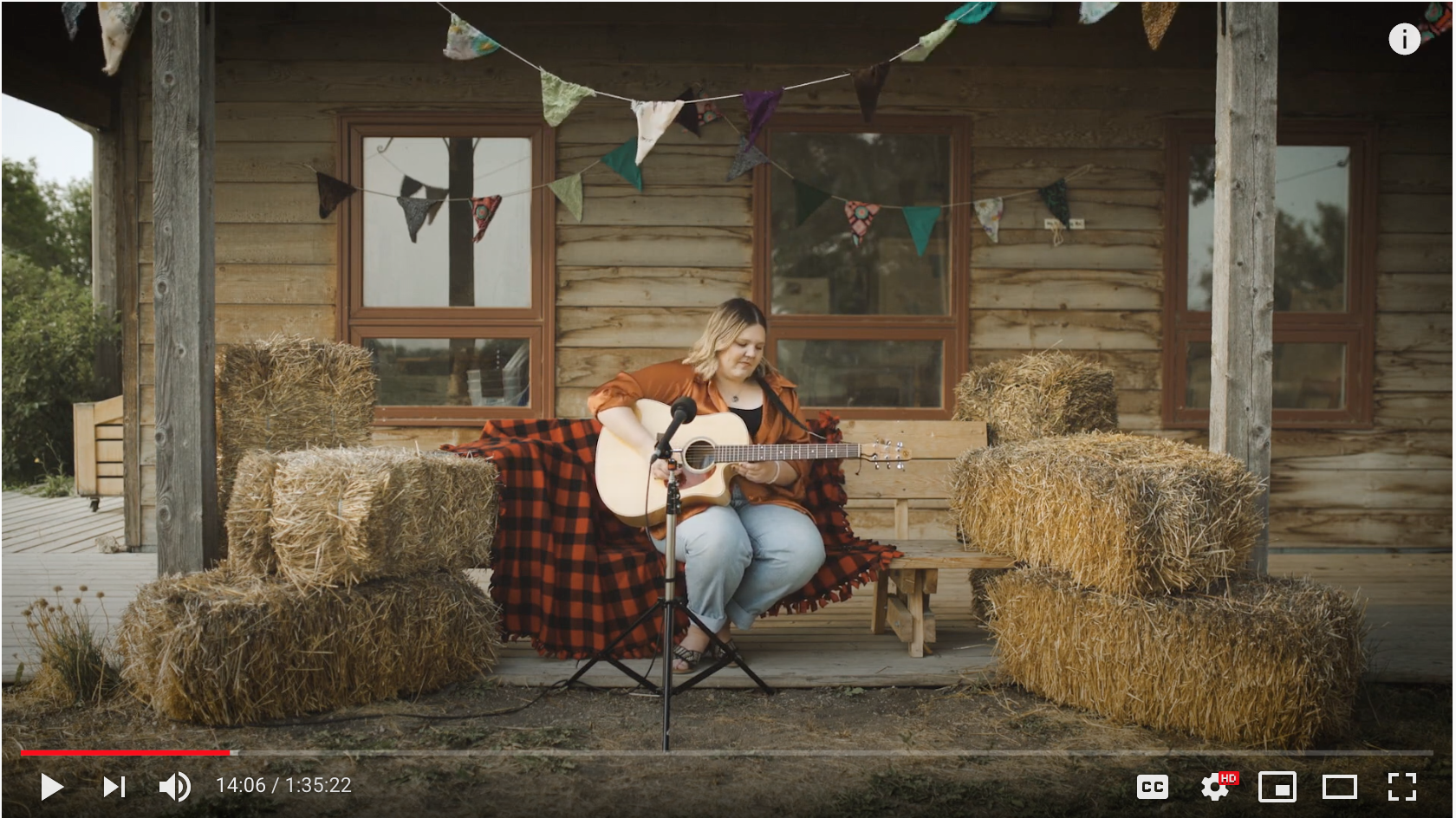 A screenshot of the Livestream on Youtube. Lana Winterhalt plays guitar surrounded by haybales outdoors.