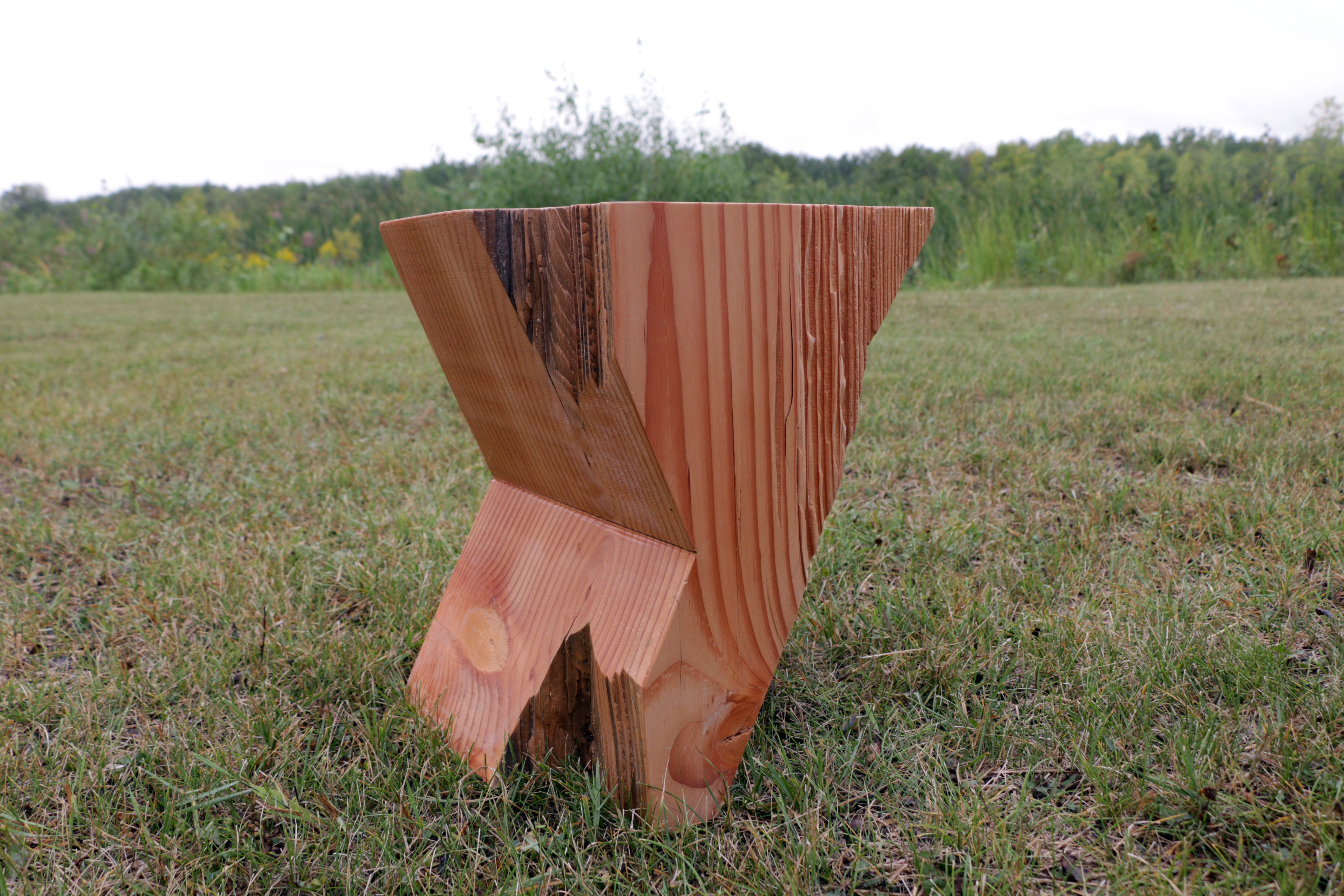 A traditional milk stool made of a solid piece of timber.