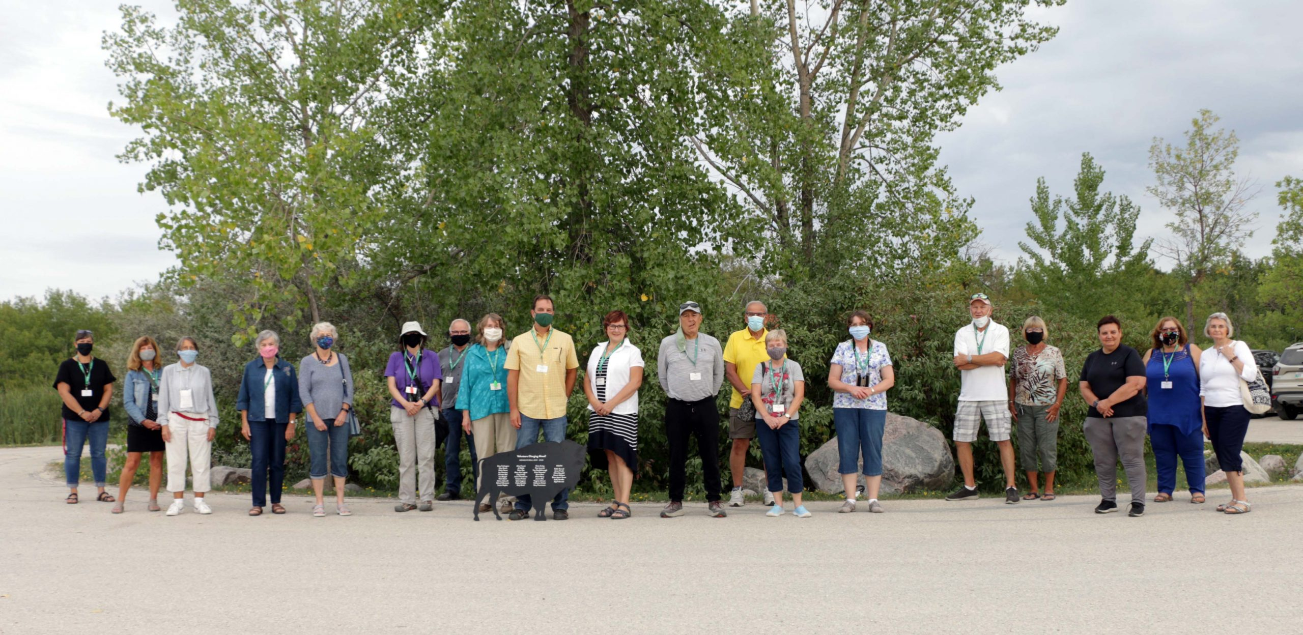 A group of volunteers who donated over 100 hours of their time stand together side by side.