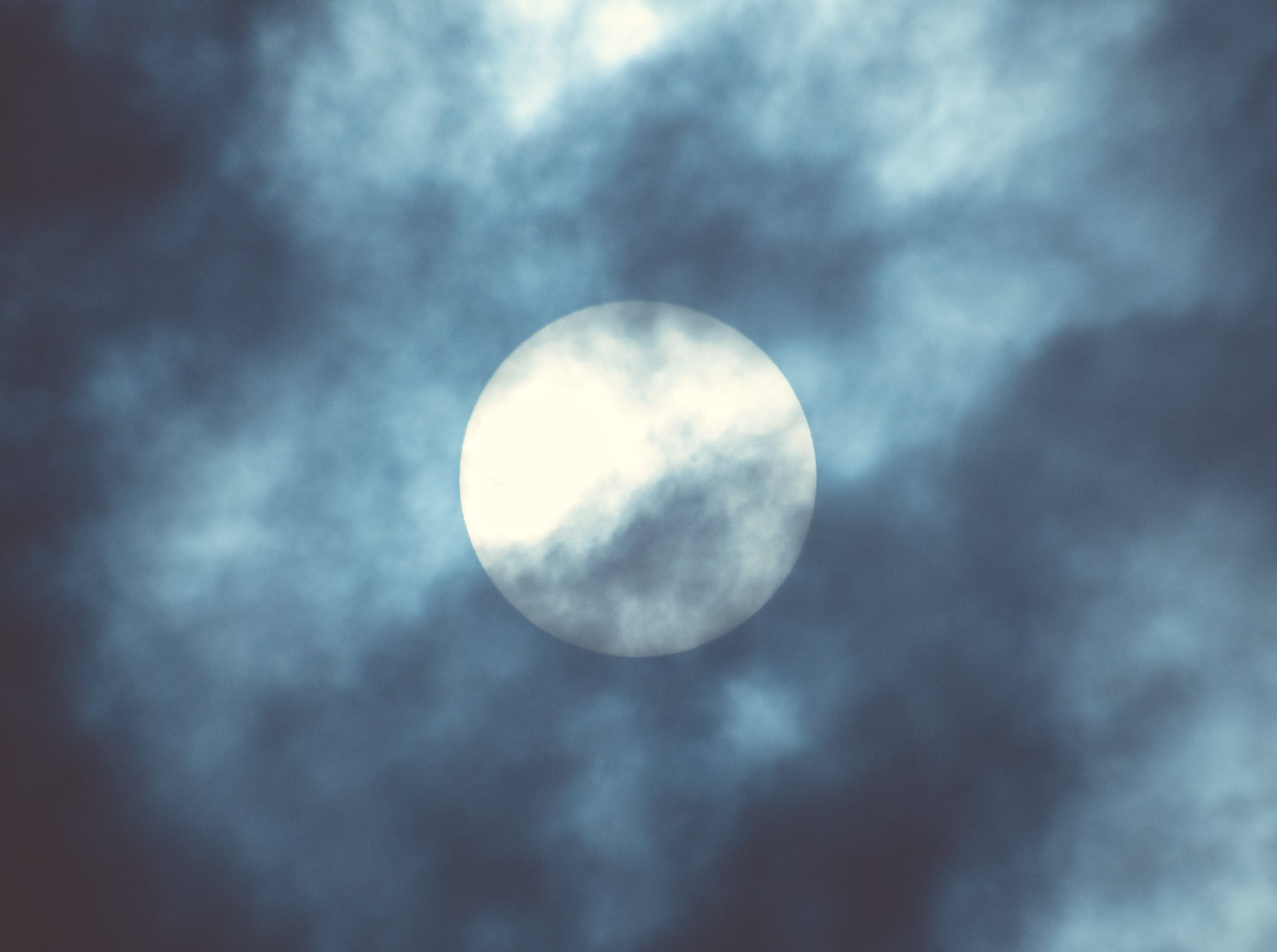 A full moon shines brightly through clouds in the sky.