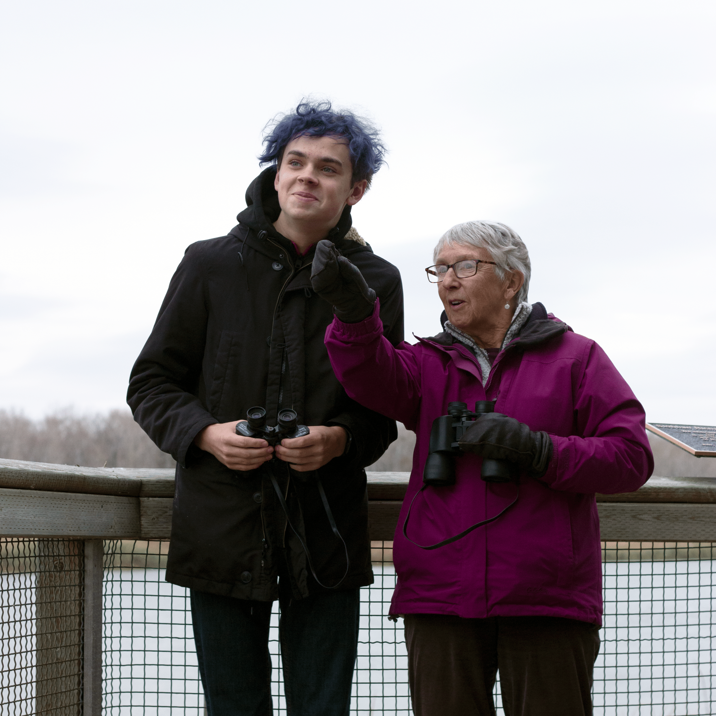 Teenager and grandmother birding over a lake at FortWhyte Alive.