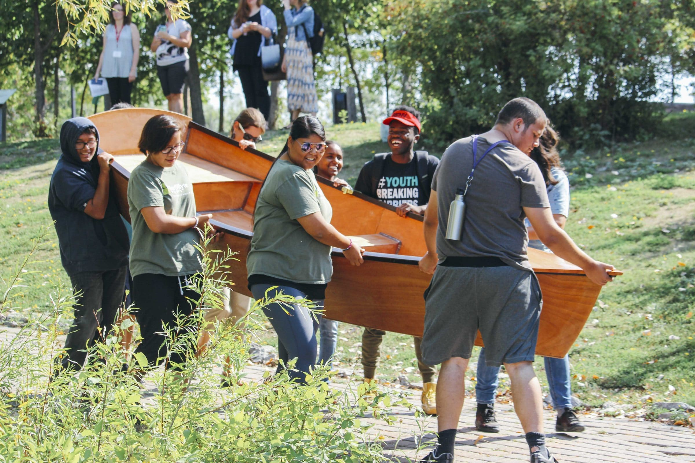 A group of FortWhyte Farm youth carry the boat they built.