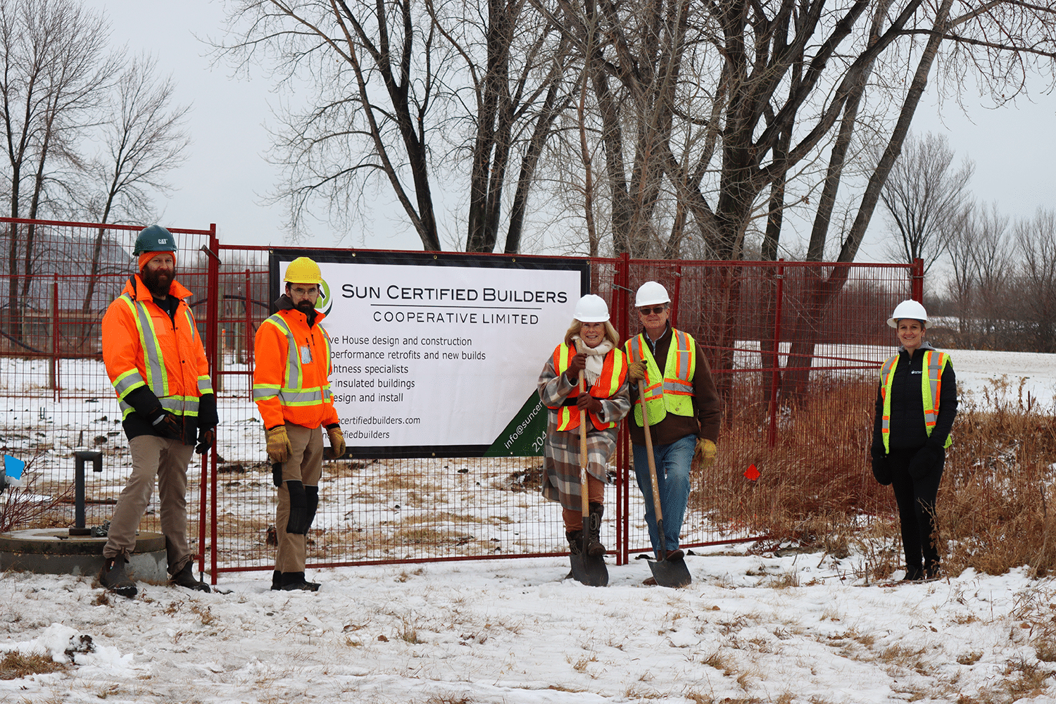Two Sun Certified employees, Marnie and Bob Puchniak, and Liz Wilson from FortWhyte Alive stand in front of the building site for the new woodworking studio. All wear bright orange vests and hard hats.