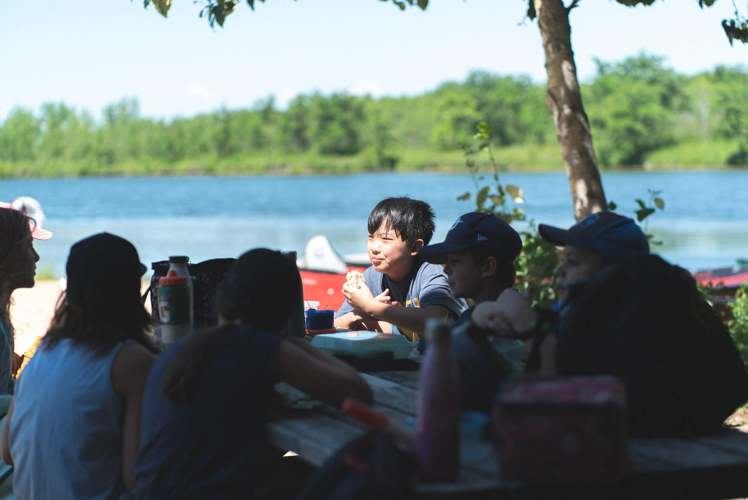 Children sitting around a picnic table eating lunch together at summer camp.