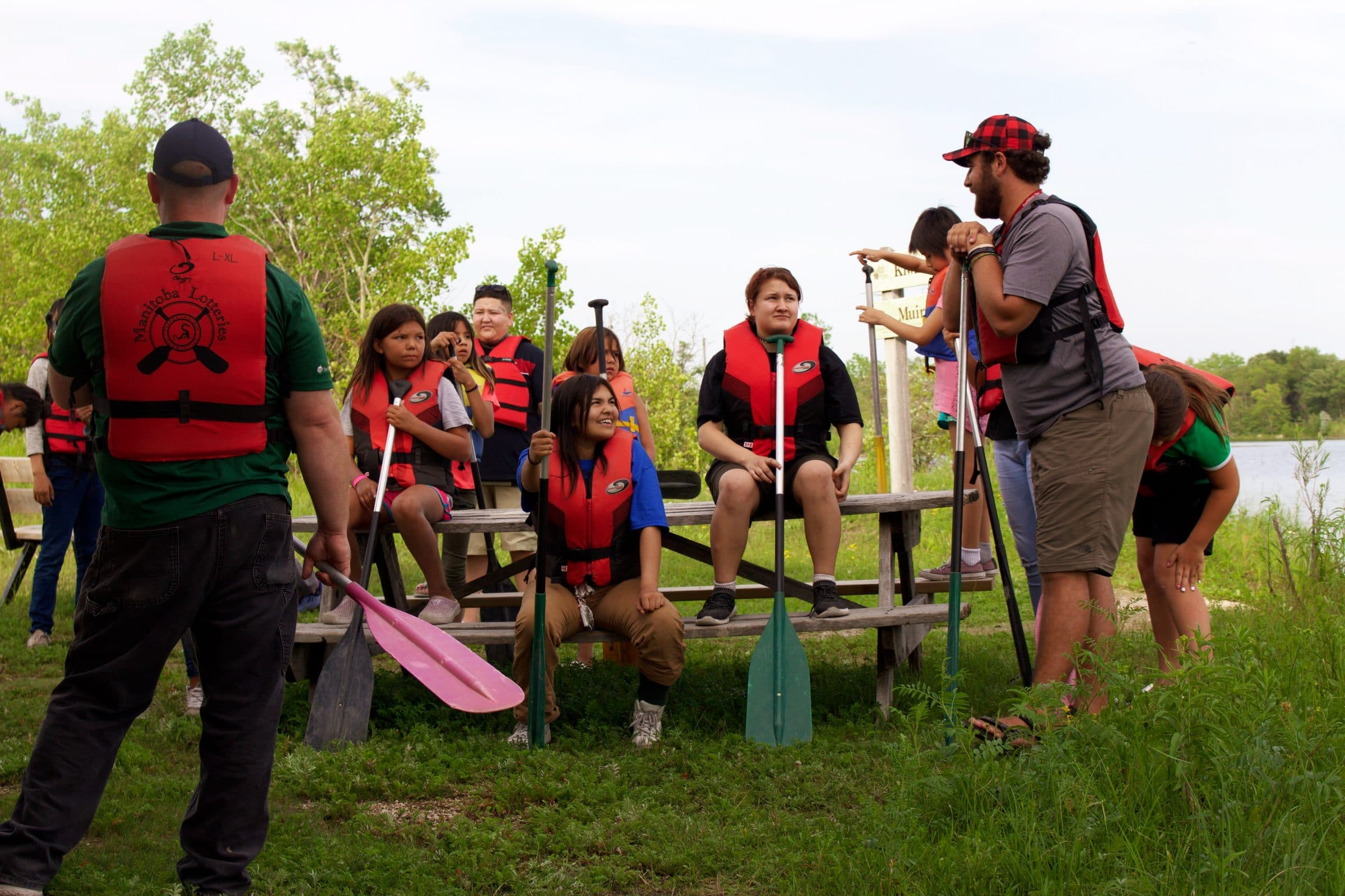 A group of youth and adults gather around a picnic table wearing life jackets, smiling and laughing together.