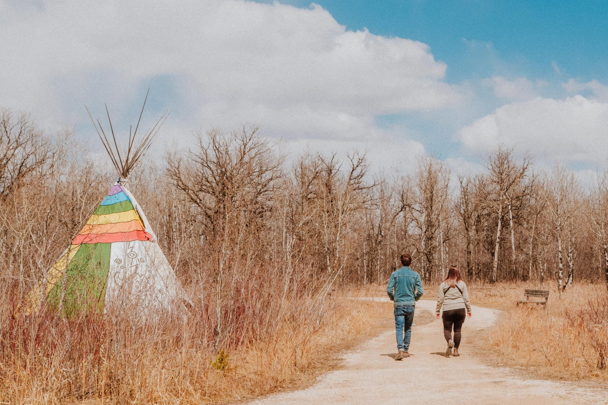 Two adults walk on the trail in spring time. A colourful painted tipi is to their left, partially hidden in tall grasses.