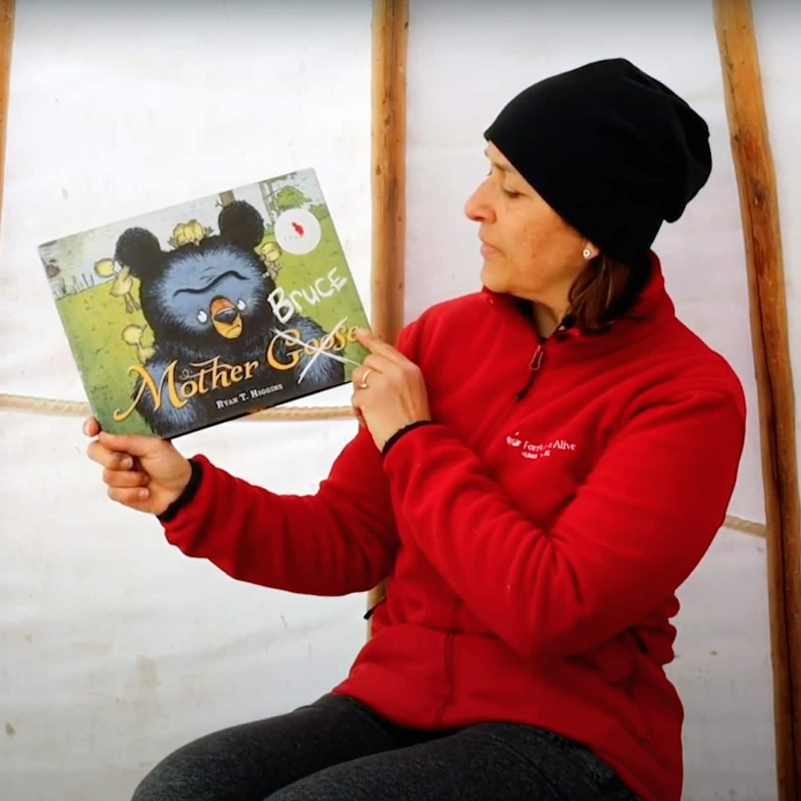 A Forest School Facilitator holds up a children's book.