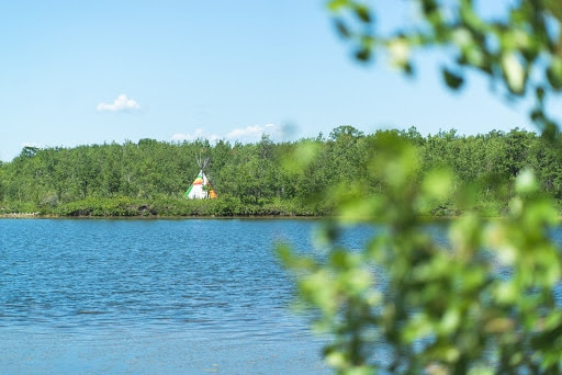 A blue lake leads to a colourful tipi in the distance, surrounded by green leafy trees.