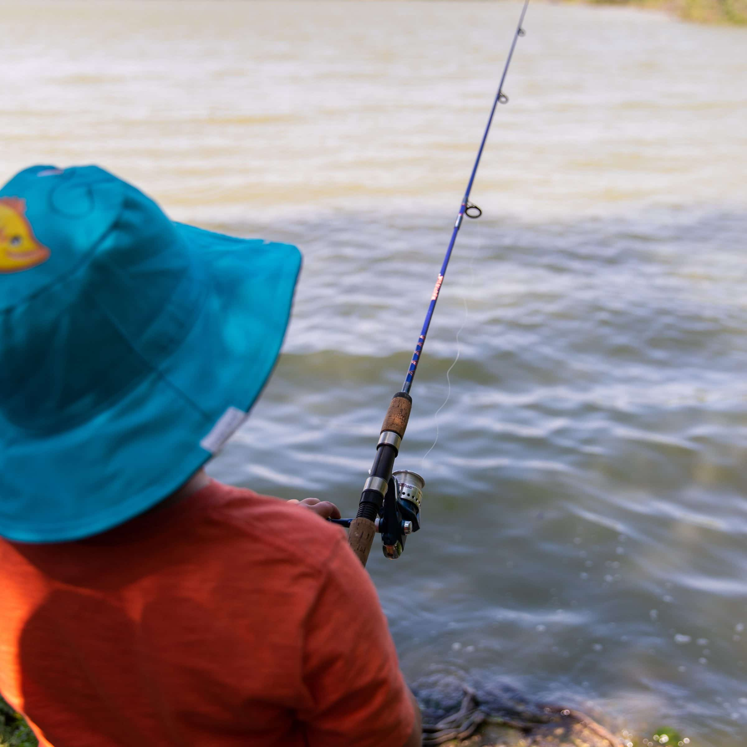 A child wearing a blue hat holds a fishing rod by the lake.