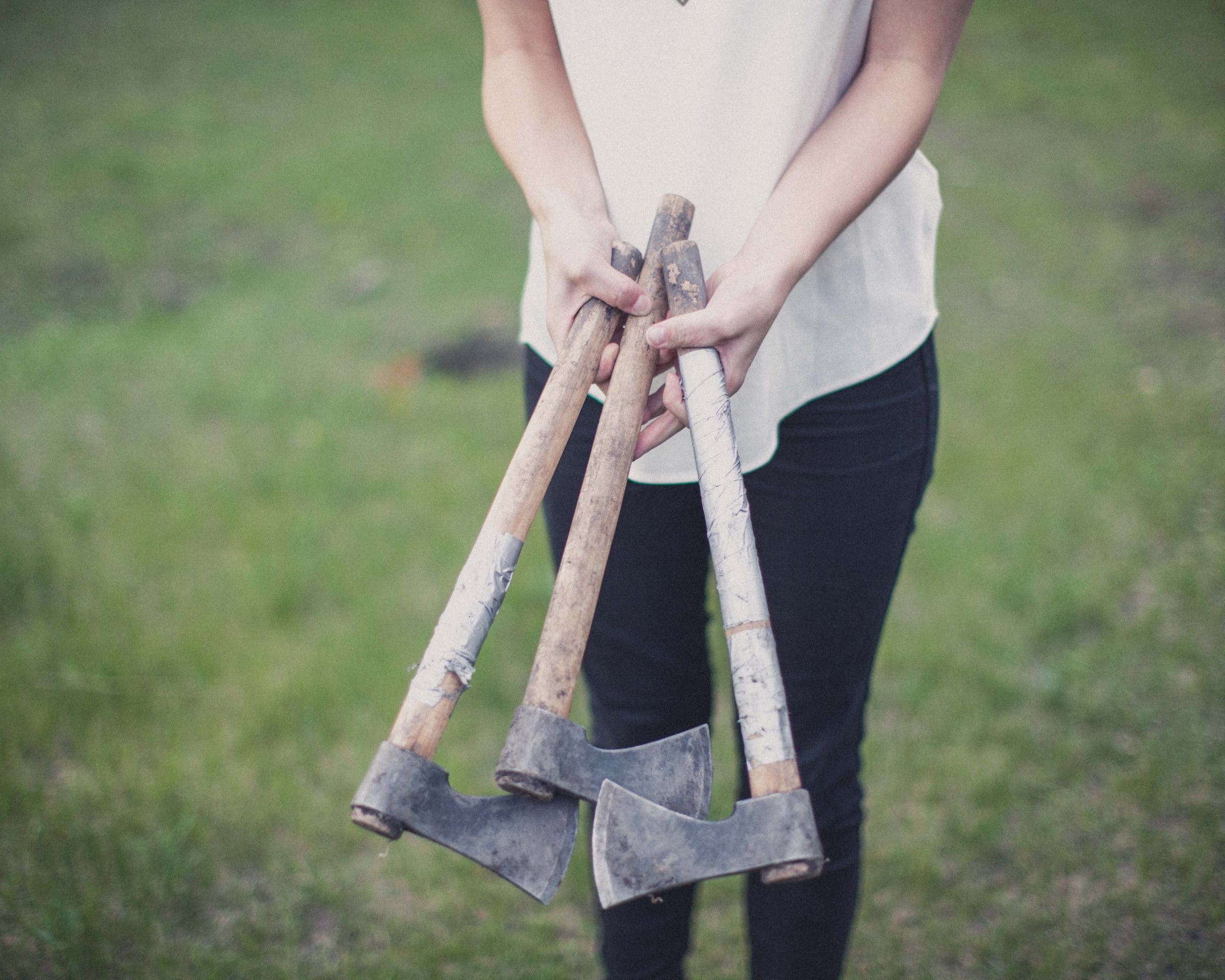An adult holds three hatchets by the handle out in front of them.