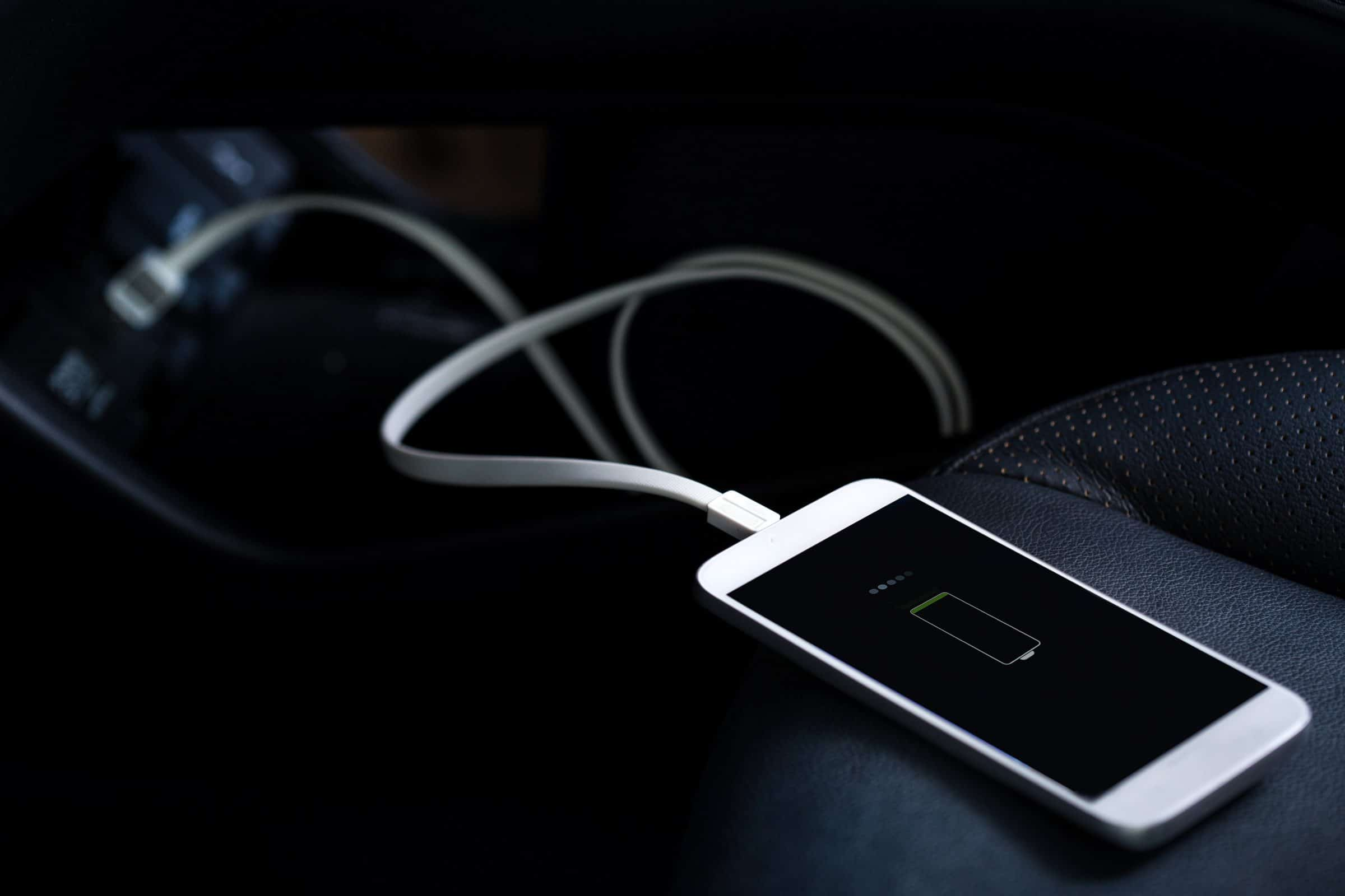 An iPhone on low batter is plugged into a car charger.