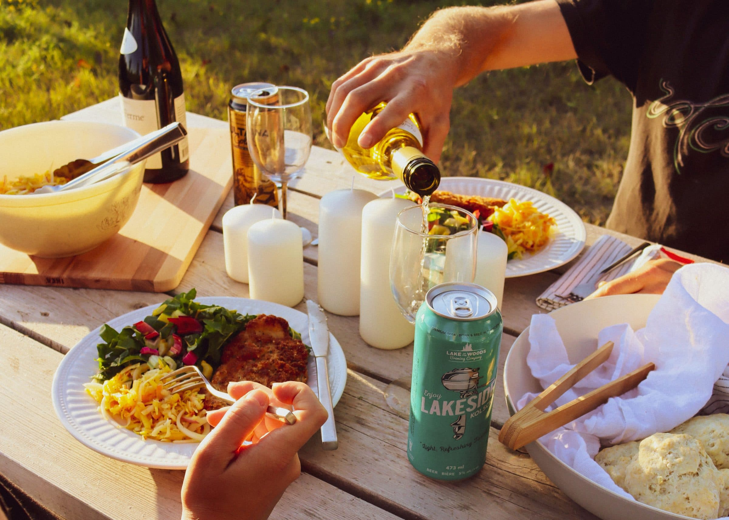Wine is being poured into a glass at sunset with various beverages and plates of food on a picnic table.