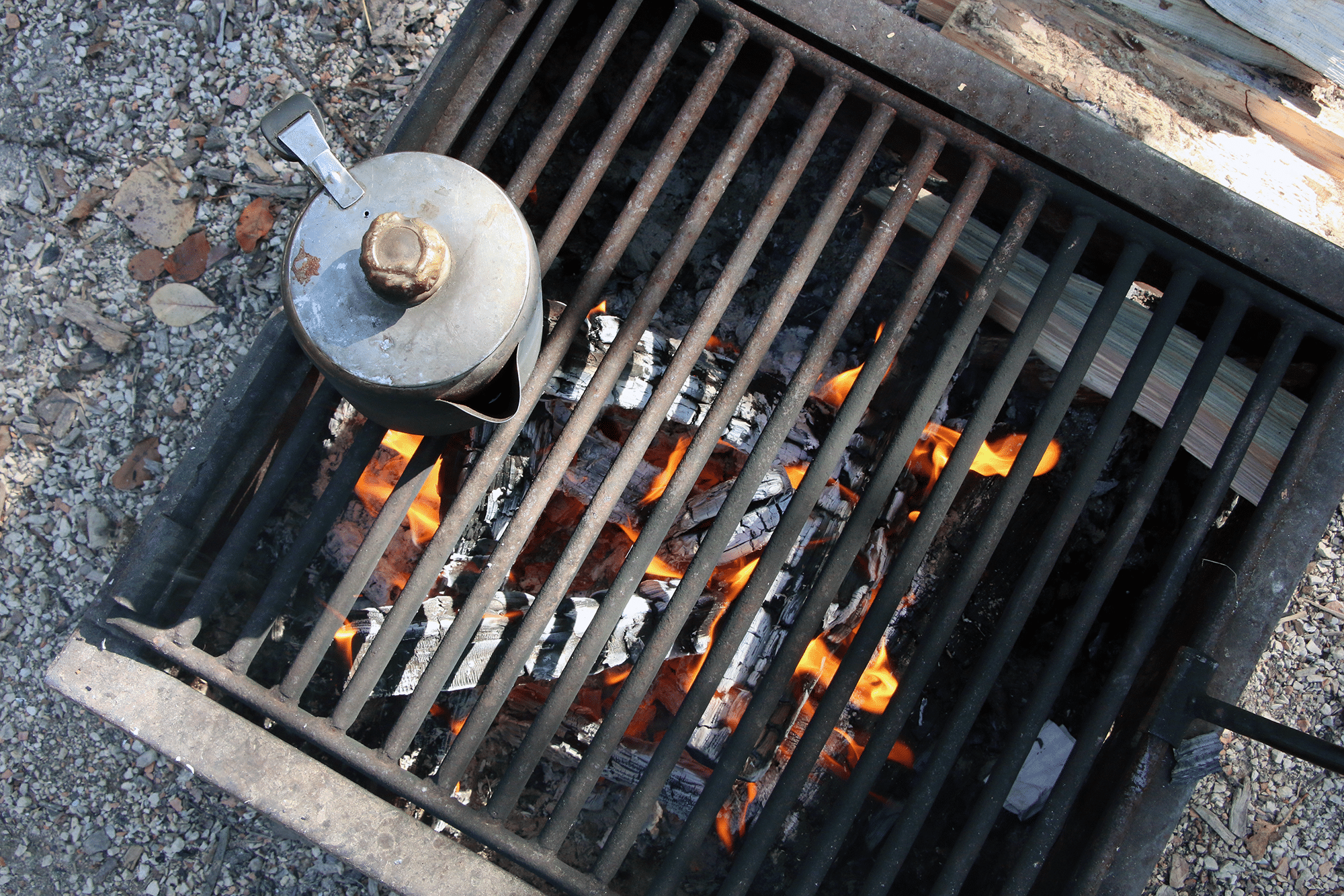 An old kettle sits on the rack of the firepit.