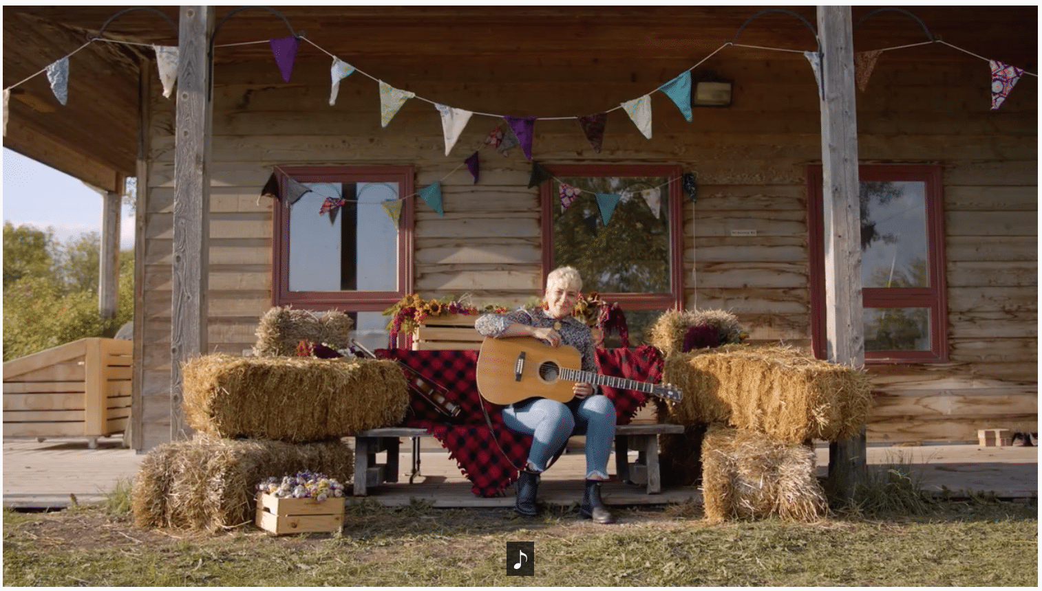 Sierra Noble plays their guitar sitting on the bench, surrounded by bales of straw and flowers from FortWhyte Farms.