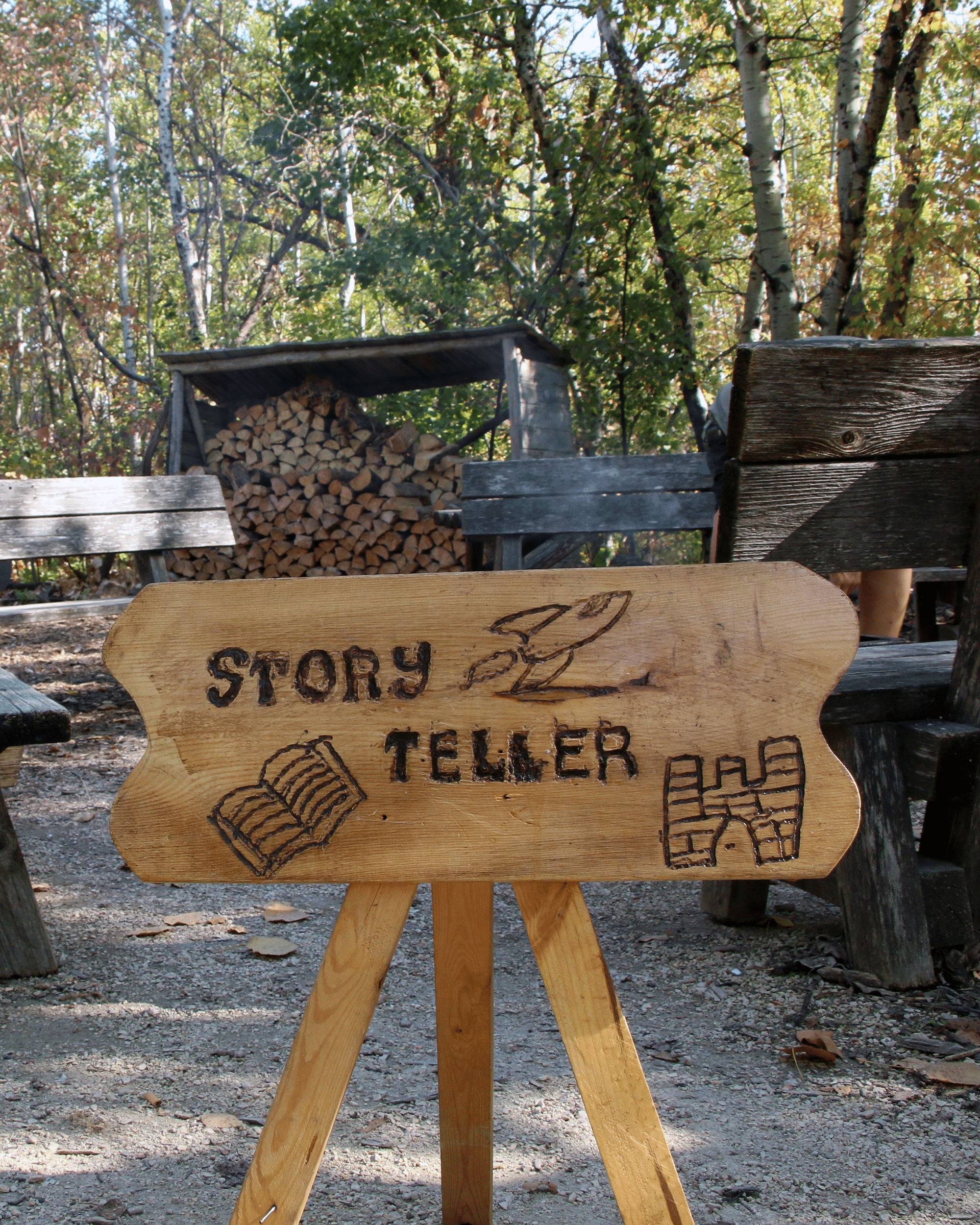 A wooden sign has Storyteller etched into it.