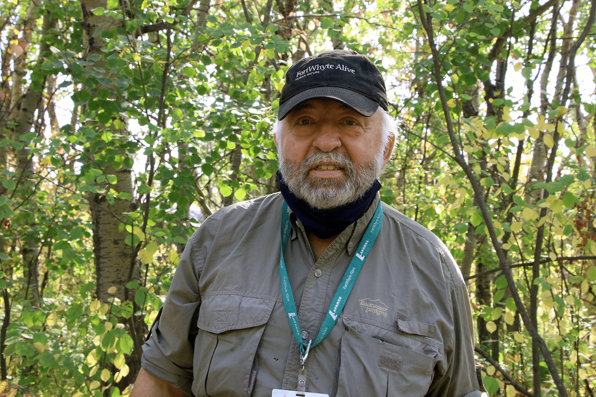 Keith wears his FortWhyte Alive Volunteer lanyard and smiles at the camera.