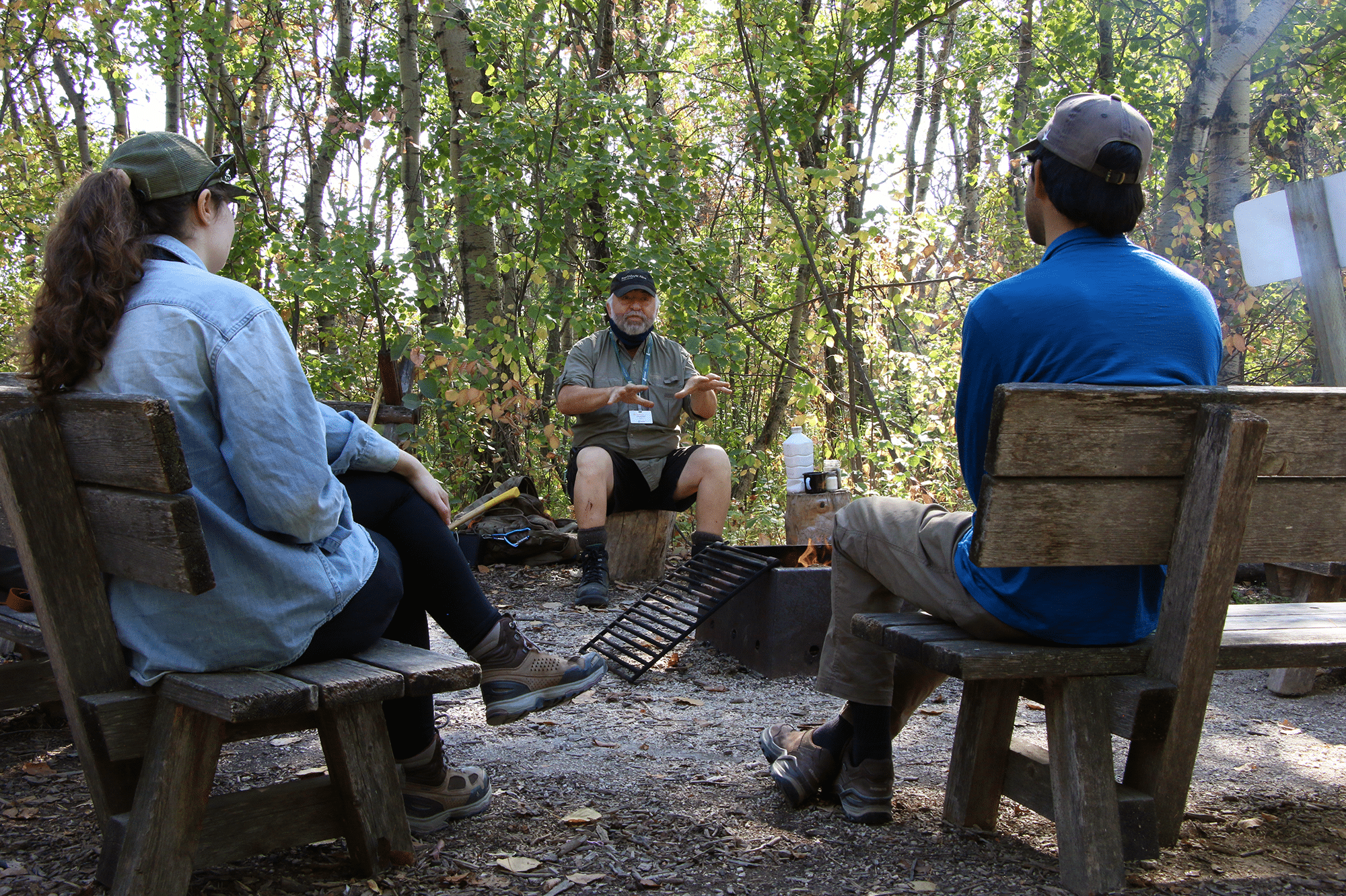 Keith tells a story to two adults sitting on different benches. Green leafy trees are behind Keith with a firepit in the middle.