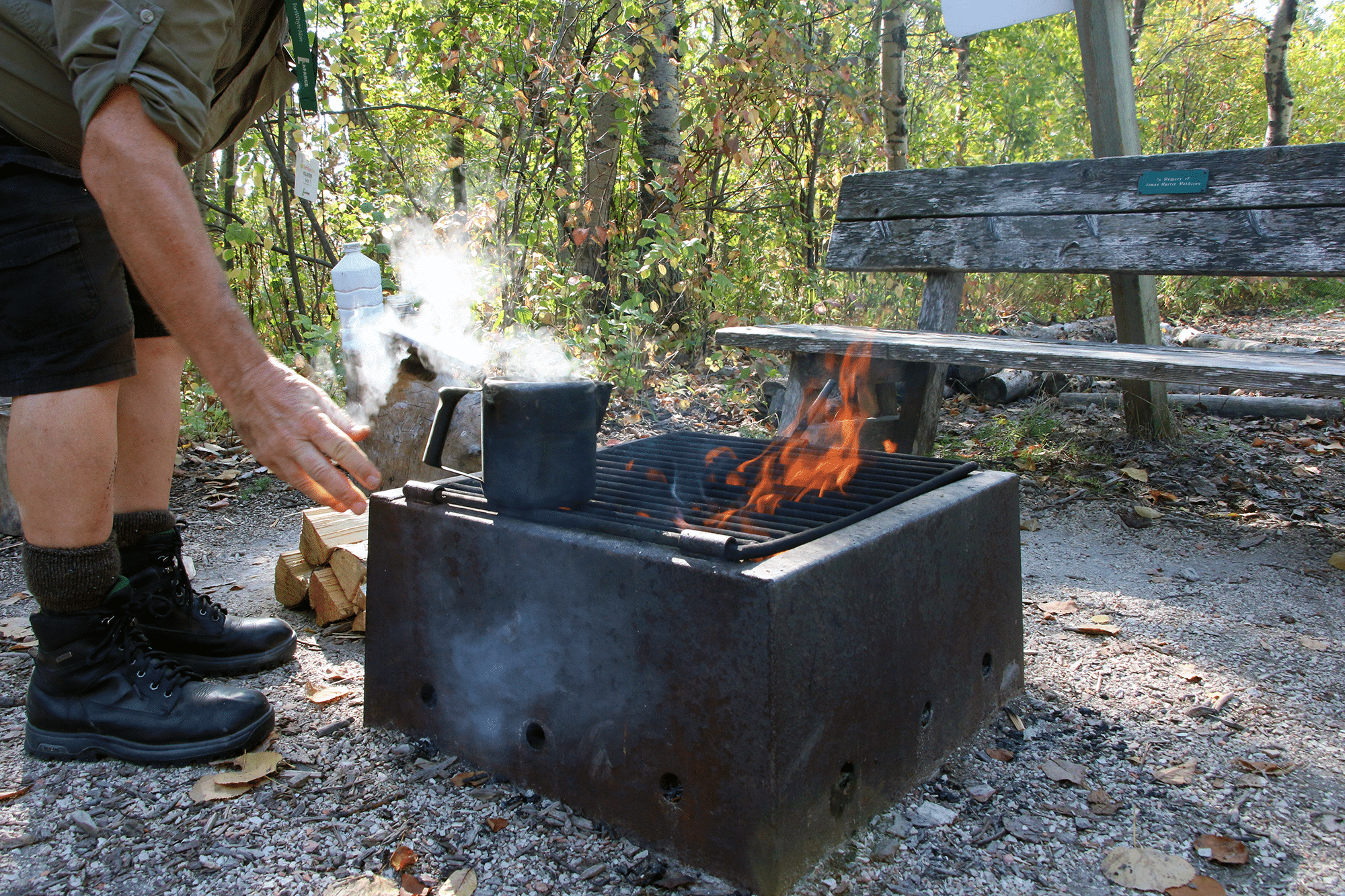 Keith opens his kettle on the firepit, releasing white steam in the sunlight.